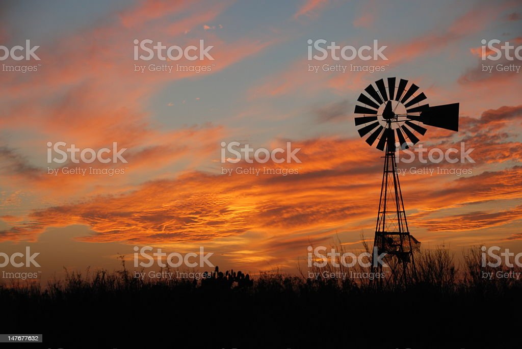 A windmill at dusk with clouds in the sky stock photo