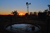 Windmill and water station at sunset