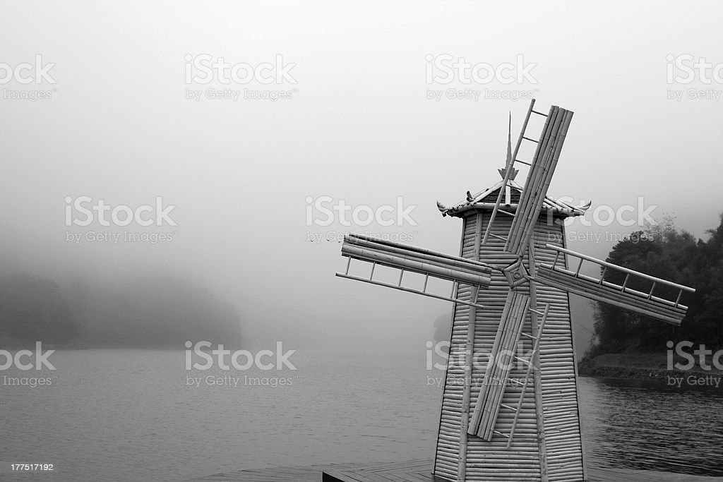 windmill beside river in the coming fog royalty-free stock photo