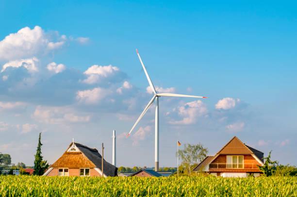 eine windmühle zwischen einfamilienhäusern an einem sonnigen tag. blauer himmel mit wolken im hintergrund.  im norden von hamburg auf dem deich des flusses elbe. - reifen hamburg stock-fotos und bilder