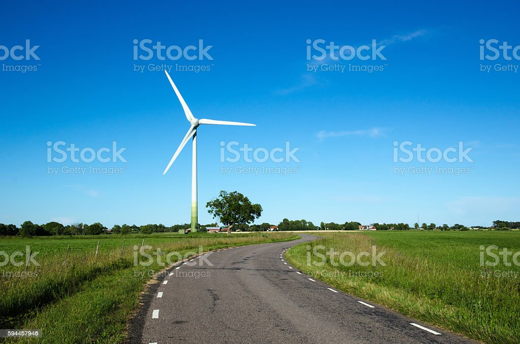 Windmill by a country road side stock photo