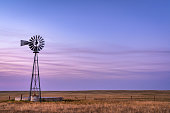 windmill with a pump and cattle water tank in shortgrass prairie, Pawnee National Grassland in northern Colorado, summer dusk scenery