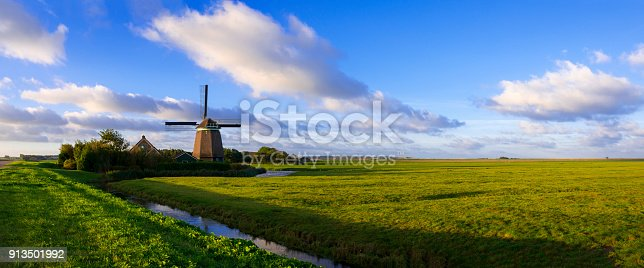 Panoramic of a windmill in a typical Dutch polder landscape with a meadow and a ditch under a nicely clouded sky