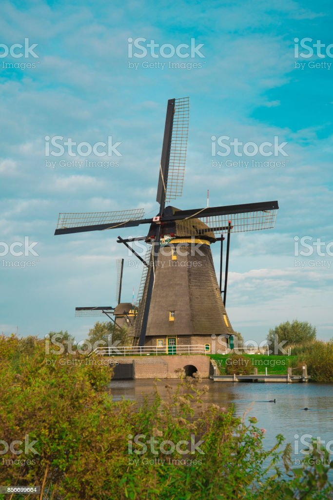 Windmill in Dutch polder water landscape, Kinderdijk, The Netherlands, against cloudy sky stock photo