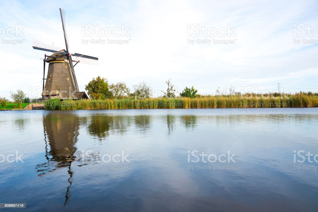Windmill in Dutch water landscape, Kinderdijk, The Netherlands, against cloudy sky stock photo