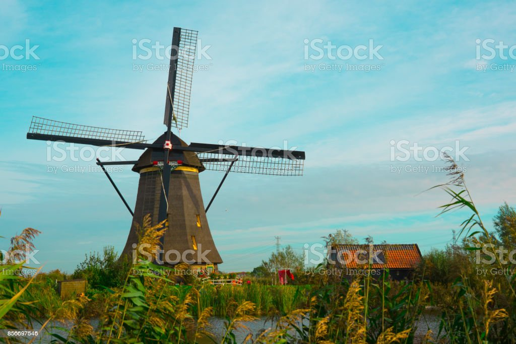 Windmill in Dutch water landscape, Kinderdijk, The Netherlands, against blue sky stock photo