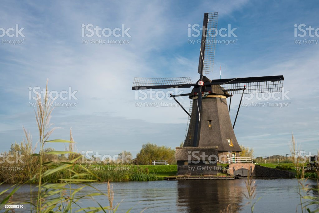 Windmill in Dutch water landscape, Kinderdijk, The Netherlands, against blue cloudy sky stock photo