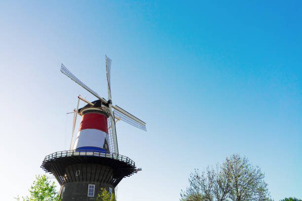 Windmill of Leiden Windmill of Leiden wrapped in Netherlands three colored flag, Holland Netherlands leiden stock pictures, royalty-free photos & images