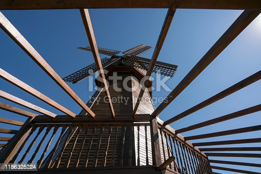 Windmill and tree construction, low angle view, blue sky