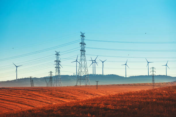 Windmühlenstromaggregat auf Grünland, Stromleitungen und Getriebeturm – Foto