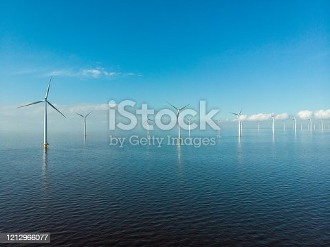 istock Windmill row of windmills in the ocean by the lake Ijsselmeer Netherlands, renewable energy windmill farm Flevoland 1212966077