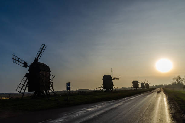 Windmill silhouettes by roadside stock photo