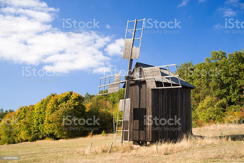 Windmill standing on the edge of the autumn forest stock photo