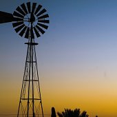 Windmill with a calm, desert sunset in the background.