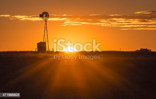 The sun sets near a windmill in the Texas Hill Country