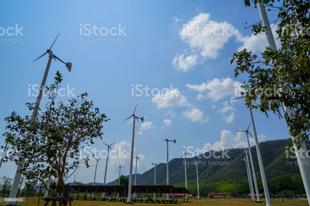 Windmill white post and solar cell panel technology to generate clean renewable ecological energy on grass yard with green mountain, blue sky and white cloud background stock photo