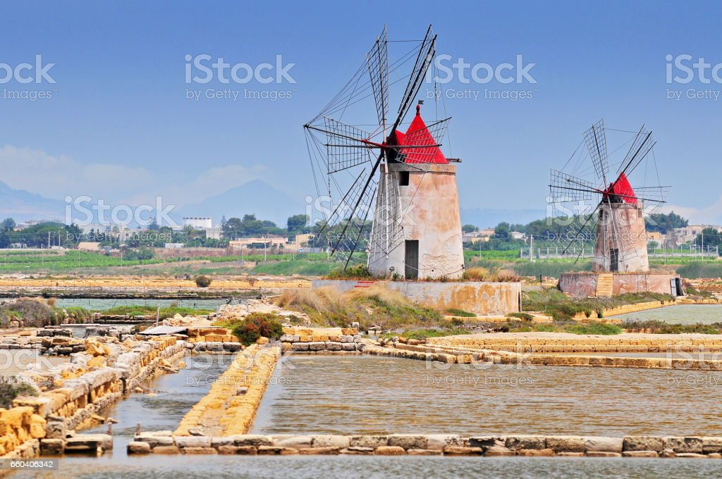Windmills and the oldest Europe's salt ponds in Sicily Italy. stock photo