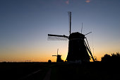 Beautiful evening scene of classic dutch windmills with a twilight sky as background.
