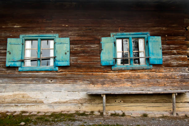 Window and a bench in front of an old log cabin stock photo