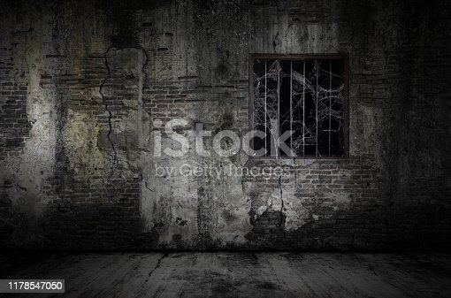 Window and rusty bars covered with cob web or spider web on prison old bricks wall and dusty floor, concept of horror and Halloween