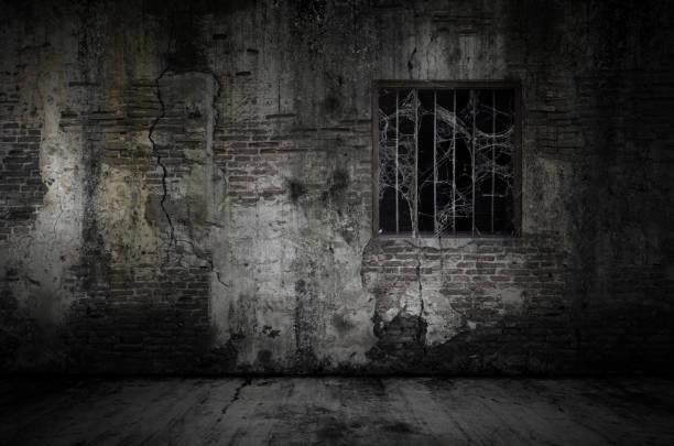 Fenster und rostige Stangen mit Kopfkolbennetz oder Spinnennetz auf Gefängnis alten Ziegelwand und staubigen Boden bedeckt – Foto