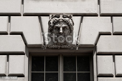 Window, carving and facade of the William Jefferson Clinton Building, Washington D.C..  The building is the headquarters of the Environmental Protect Agency (EPA).  Constructed in 1934, this neoclassical building was designed by William Adams Delano and Chester Holmes Aldrich.   The relief carvings were designed by Adolph Alexander Weinman.