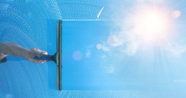 window cleaner cleaning window with squeegee and wiper on a sunny day stock photo