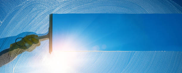 Window cleaner cleaning window with squeegee and wiper on a sunny day with a bright blue sky. stock photo