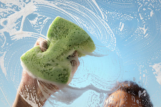 Window cleaner using a sponge and soap suds to wash a window stock photo