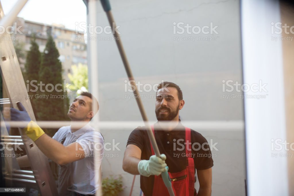 Window cleaners working together stock photo