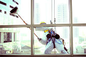 """Man at work, cleaning building windows."""