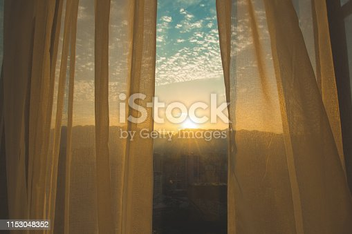Window curtain at sunrise