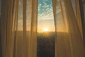 Window curtain at sunrise
