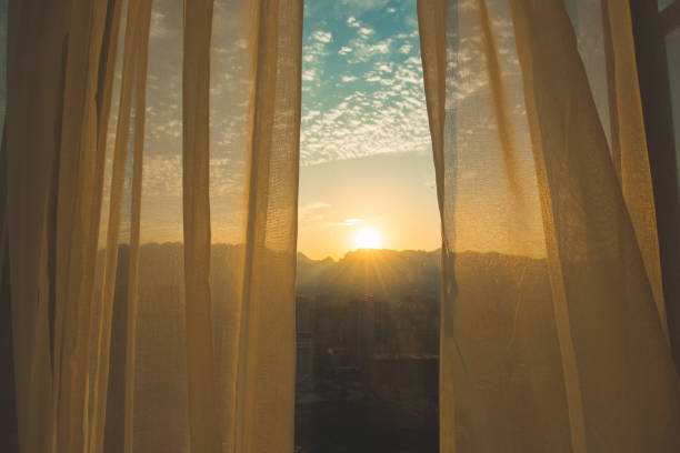 Window curtain at sunrise Window curtain at sunrise dawn stock pictures, royalty-free photos & images