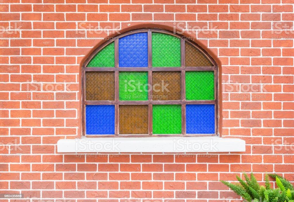 Janela decorada com vitrais na parede de tijolo. - foto de acervo