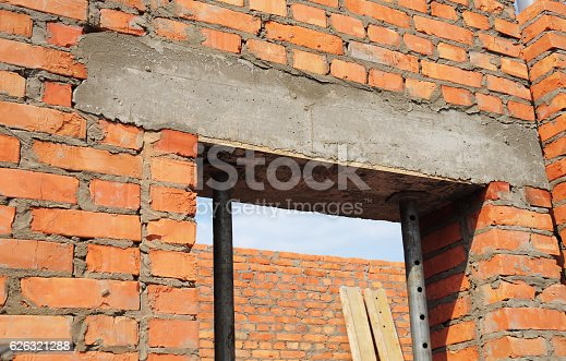 Building house construction. Window, door concrete lintel with iron bar on brick unfinished house construction.