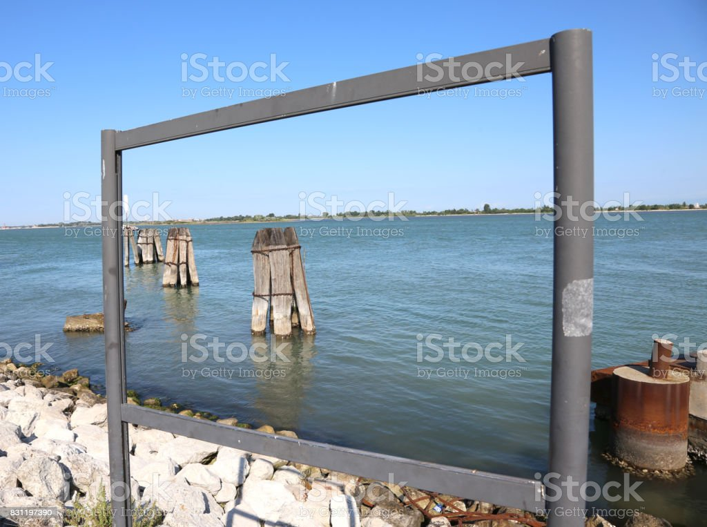 Window frame on Venetian lagoon with poles in the sea stock photo
