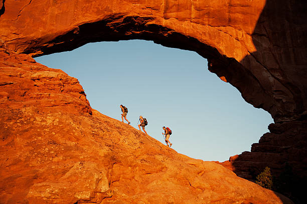 Window Hikers Three hikers explore the North Window at sunrise in Arches National Park. arches national park stock pictures, royalty-free photos & images