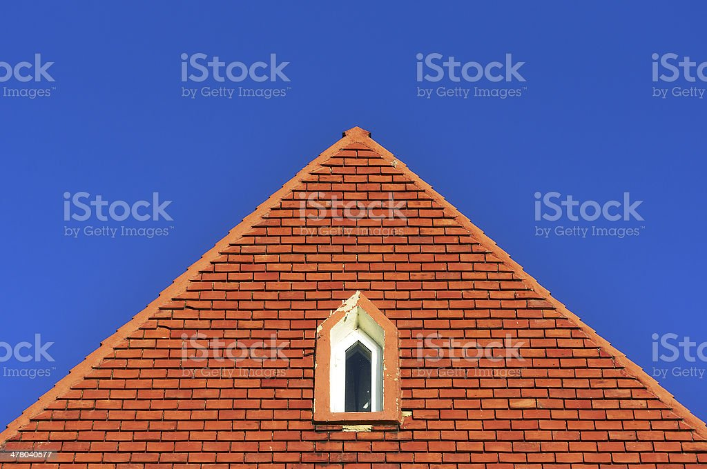 window in a roof attic with bricks royalty-free stock photo