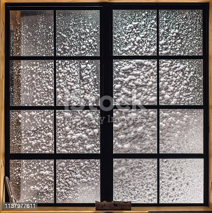 Window with square pane at night in a snow storm