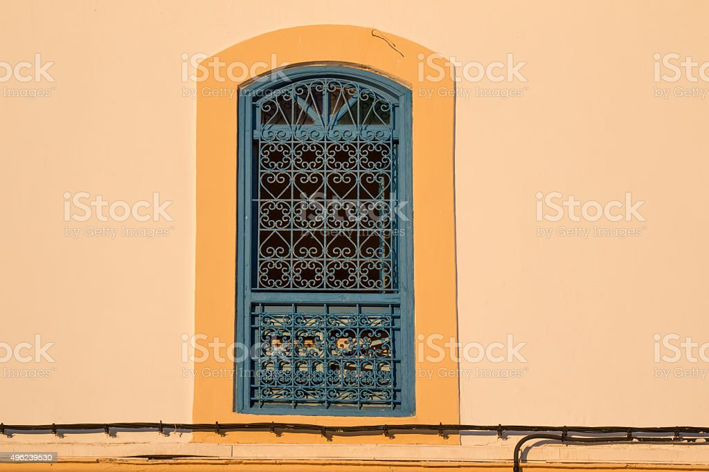 Contrast of the yellow facade with the traditional grating of the...