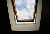 Window in the ceiling. Blue sky with clouds. Attic interior.