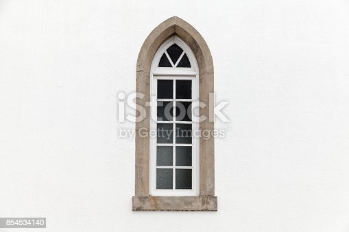 Window in white stone wall, Gothic Revival architecture style. Background photo texture