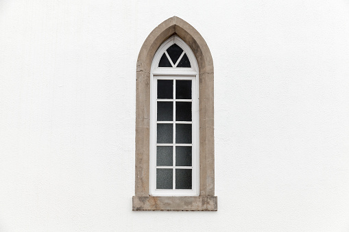 Window in white stone wall, Gothic Revival