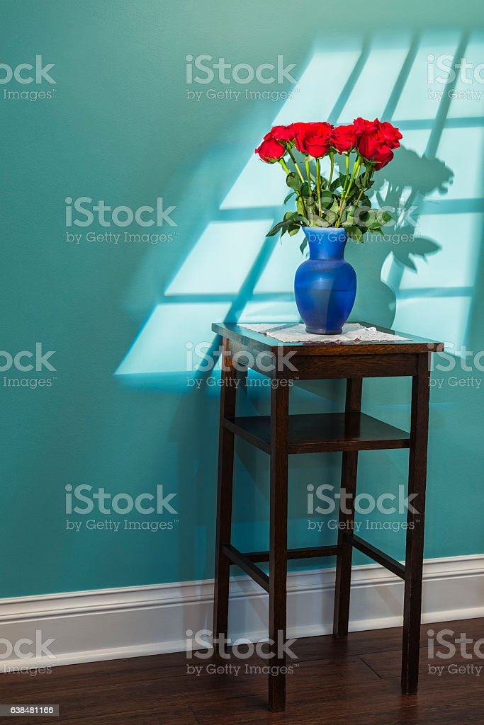 Window light shining on a dozen red roses on table stock photo