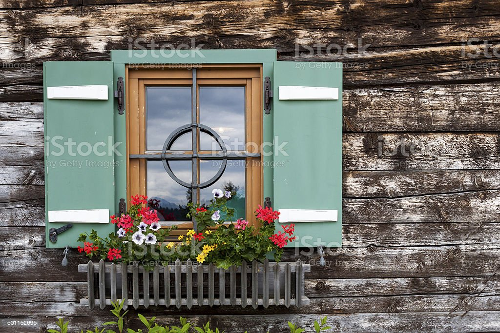 Window of a wooden hut in the Alps stock photo