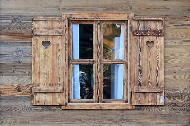 Window of a wooden hut with hearts in the blinds Open window of a wooden hut with hearts in the blinds chalet stock pictures, royalty-free photos & images