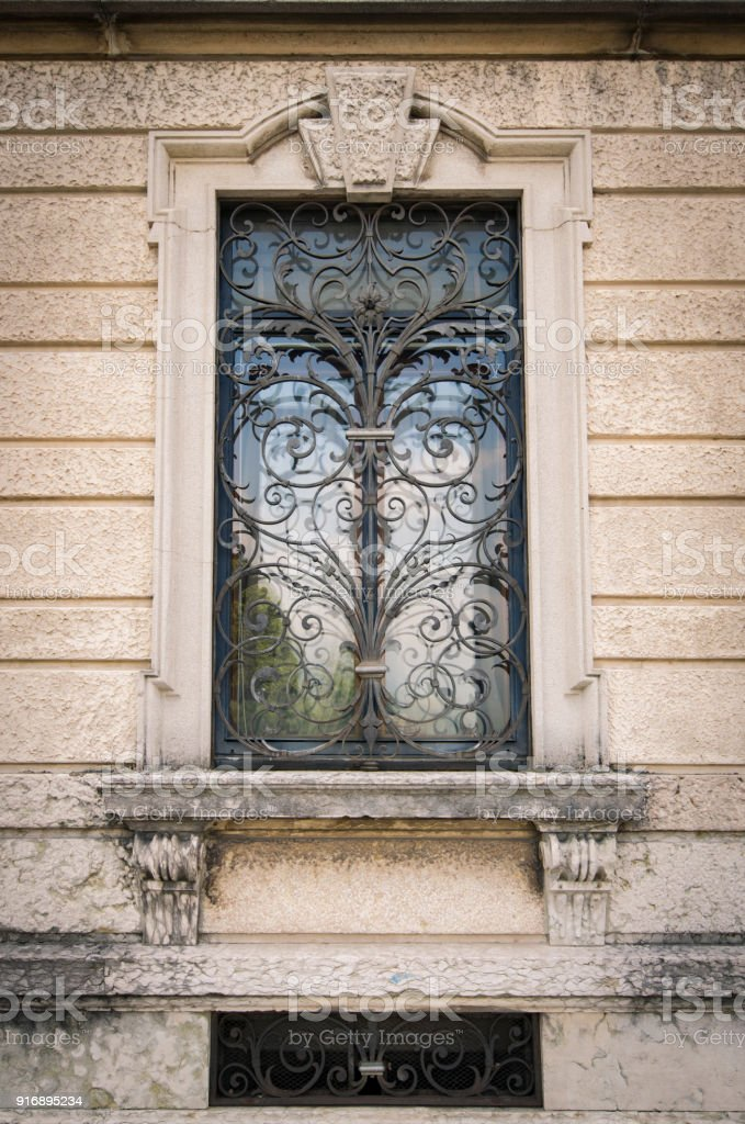 Window of an ancient Italian villa with artistic iron grill. stock photo