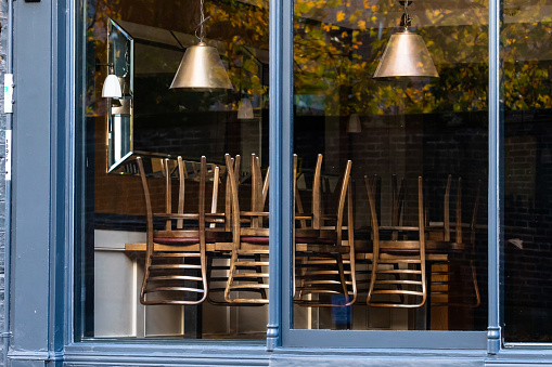 Chairs on the tables of a restaurant forced to close during lockdown to control COVID-19 pandemic, Cambridge, UK