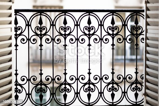 Close-up shot of windows opening up onto balcony in parisian home.